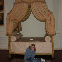 Megan poses by a fancy bed at the Museum of Paris