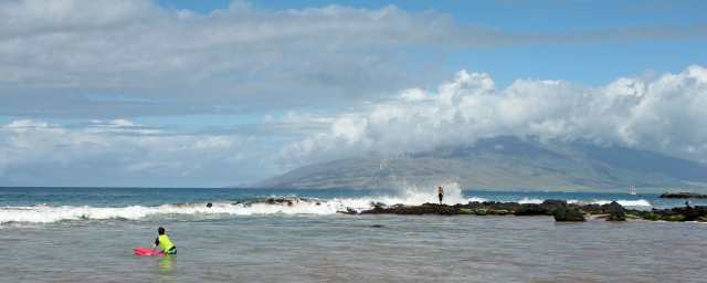 Here is the spectacular view at our beach.  The mountains in the distance are the West Maui Mountains.  Notice the windfarm climbing up the ridge.  The older man standing on the lava point was about as close as you could get the pounding surf without being swept away ... maybe too close!