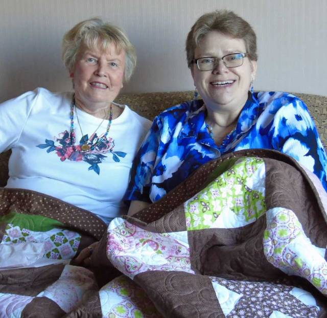 The Kid and her dear friend, Barb, met again  after many years.  They're sitting under a quilt Barb made for Krista as a gift.